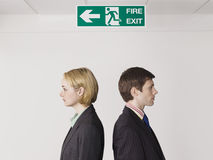 Business Colleagues Standing Under Exit Sign Royalty Free Stock Photography