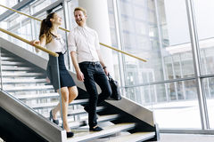 Business colleagues talking on stairs. And flirting while smiling Royalty Free Stock Photos