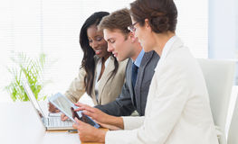 Business colleagues using laptop and digital tablet at desk Royalty Free Stock Photo