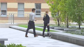Business colleagues walking on the street of an business center. slow motion. Two business colleagues in discussion, businesspeople walking on the street of an stock footage