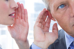 Business colleagues whispering Stock Images