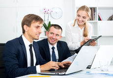 Business colleagues and woman standing with cardboard Royalty Free Stock Photos