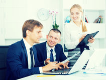 Business colleagues and woman standing with cardboard Stock Photos