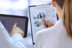 Business colleagues working and analyzing financial figures on a graphs Stock Photo