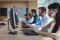 Business colleagues working at call center. Business colleagues working at desk in call center royalty free stock photos