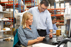 Business Colleagues Working At Desk In Warehouse. Talking Royalty Free Stock Image