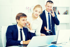 Business colleagues working and discussing on phone Stock Images