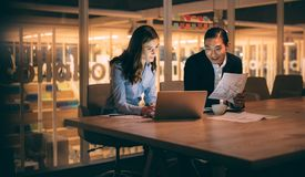 Business colleagues working late night in office. Businessman and woman discussing business work sitting late in office. Woman entrepreneur working on laptop stock image