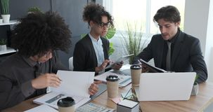 Business colleagues working at office. Businessmen and businesswoman looking at report using laptop and digital tablet at office stock video footage