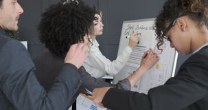 Business colleagues working over financial reports on office whiteboard. Businessmen and businesswomen working over financial reports on whiteboard at office stock footage