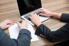 Business colleagues are working on the project. A laptop and a blank paper are on the table. Royalty Free Stock Images