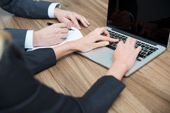 Business colleagues are working on the project. A laptop and a blank paper are on the table. Stock Image
