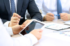 Business colleagues working together and analyzing financial figures on a digital tablet Royalty Free Stock Photos