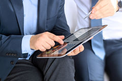 Business colleagues working together and analyzing financial figures on a digital tablet Stock Photos