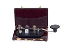 Business communication. Shown by an antique telegraph key in a briefcase - path included Stock Images