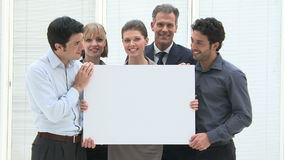 Business communication. Happy smiling business team holding a blank placard ready for your text or product. Businesspeople holding a white placard and looking at stock video
