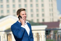 Business communication and new technology. Happy businessman with smartphone on sunny terrace. Man smile in formal suit with mobil. E phone outdoor. Business stock photo