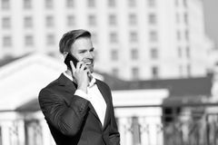 Business communication and new technology. Happy businessman with smartphone on sunny terrace. Man smile in formal suit. With mobile phone outdoor. Business royalty free stock image