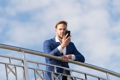 Business communication, new technology, sms. Man with smartphone on terrace on blue sky, business communication. Businessman in business suit with mobile phone stock image