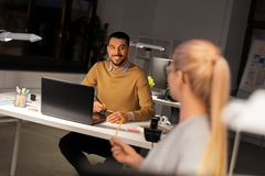 Designer with laptop talking to coworker at office royalty free stock image