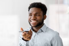 Businessman records voice by smartphone at office. Business, communication and technology concept - african american businessmanr calling or using voice recorder Stock Photo