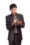 Business communication. Young businessman in dark grey suit stands with mobile phone isolated on white background Royalty Free Stock Image