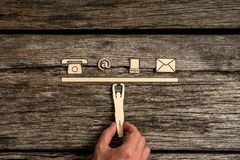 Business communications and contact concept. With a businessman supporting a cut out of a man holding up a line of phone, web and mail icons on rustic wood Royalty Free Stock Image