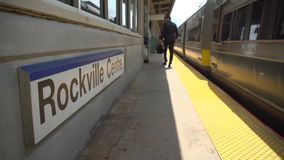 Business commuter at Rockville Centre train passing the station sign. Low view of business commuter at Rockville Centre train passing the station sign stock video