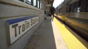 Business commuter at train station. Low view of business commuter and train passing the station sign stock footage