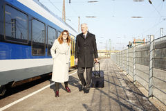 Business commuters. Full length portrait of middle aged businesswoman and senior businessman walking a train station Stock Photos