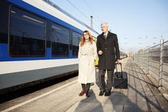 Business commuters. Full length portrait of middle aged businesswoman and senior businessman walking a train station Royalty Free Stock Photos