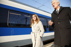 Business commuters. Portrait of middle aged businesswoman and senior businessman walking a train station Stock Images