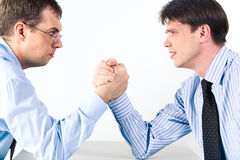 Business competition. Portrait of two businessmen sitting opposite each other elbowing on the table with their arms grappled in fight Royalty Free Stock Photography