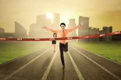 Business competition. Concept: Businessman crossing the finish line on the track Stock Photos