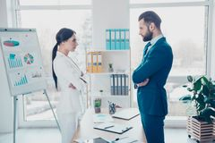 Business competition, side view profile of two colleagues in classic suits having disagreement and conflict, standing in. Workstation, workplace, face to face royalty free stock image