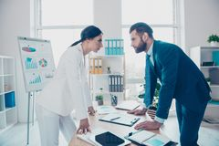 Business competition, side view profile of two colleagues in classy suits having disagreement and conflict, standing in modern. Work station, place, face to royalty free stock photo