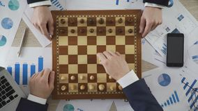 Business competitors playing chess game, company taking strategic step on market. Stock footage stock video