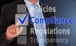 Business compliance on touch screen. Compliance checked on a touch screen slide with a businessman in the background Stock Image
