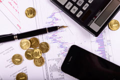 Business composition of the coins, calculator and charts. Composition of a pen and coins on the background of graphs and charts royalty free stock photography