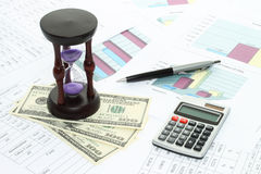 Business composition of graphs, tables, money, sand watch Stock Photography
