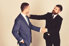 Business and compromise concept. Executives shake hands in agreement. On light grey background. Businessmen wear smart suits and ties. Men with beard and royalty free stock photography