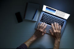 Business Laptop Computer Work Hands. Hands using a laptop computer at night or in the dark, with a business article on the screen Stock Photography