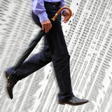 Business concept. Businessman walks across trading figures in newspaper Royalty Free Stock Images