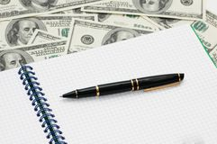 Business concept. Pen  and notebook over dollars Stock Photo
