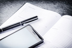 Business concept with agenda, mobile phone and pen Stock Photography