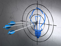 Business concept: arrows in Light Bulb target on wall background. Success business concept: arrows hitting the center of Blue Light Bulb target on wall Royalty Free Stock Photos