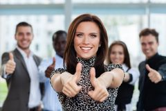 Business concept - attractive businesswoman with team in office showing thumbs up. stock images