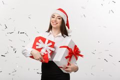 Business Concept - Beautiful young caucasian business woman with santa hat holding gift box with confetti celebration. Background Royalty Free Stock Image