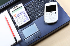 Business concept with a blue notebook, white calculator, red pen. And white mobile phone Royalty Free Stock Photos