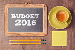 Business concept of budget for 2016 new year. Chalkboard with coffee cup on wooden desk. Royalty Free Stock Photography